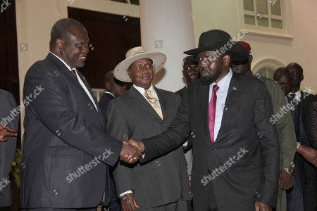 Former Vice President of South Sudan Riek Machar, left, greets South Sudan President Salva Kiir as Uganda President Yoweri Museveni, center, looks on as they meet for a security meeting to find a lasting solution to insecurity in South Sudan, at the State House, in Entebbe, Uganda