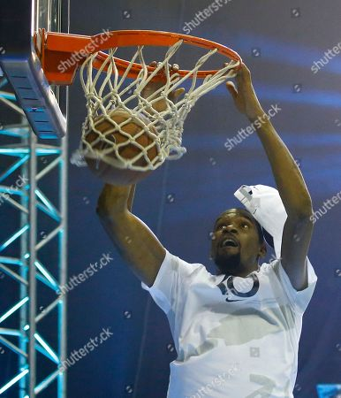 Kevin Durant scores a slam during an exhibition basketball game with Philippine basketball players at the Smart Araneta Coliseum northeast of Manila, Philippines . Durant is here for the second time to conduct basketball clinics and to launch his Nike 'KD 11' basketball shoes
