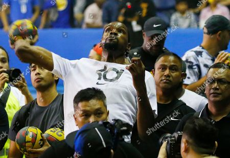 Kevin Durant throws an autographed basketball to his fans following an exhibition basketball game with Philippine basketball players at the Smart Araneta Coliseum northeast of Manila, Philippines . Durant is here for the second time to conduct basketball clinics and to launch his Nike 'KD 11' basketball shoes