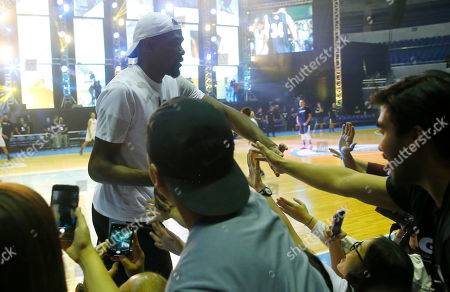 Kevin Durant greets fans prior to an exhibition basketball game with Philippine basketball players at the Smart Araneta Coliseum northeast of Manila, Philippines, . Durant is in the Philippines for the second time to conduct basketball clinics and to launch his Nike 'KD 11' basketball shoes