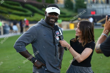 Michael Vick is interviewed on field during the American Flag Football League (AFFL) U.S. Open of Football tournament, in Kennesaw, Ga