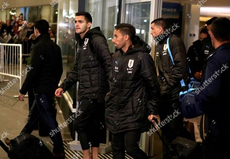 Stock Photo of Uruguay's players Maximiliano Gomez (L), Jonathan Urretaviscaya (C) and Jose Maria Gimenez are seen upon the arrival of the Uruguayan team to the airport of Montevideo from Nizhny, Russia, to the airport of Montevideo after their participation in the 2018 Russia World Cup, in Uruguay, 09 July 2018.