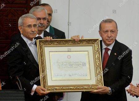 Turkish parliamentary speaker Durmus Yilmaz (L) gives the certificate of election to Turkish President Recep Tayyip Erdogan (R) after Erdogan's oath during the new Legislative Year of the 27th Term and oath ceremony at Grand National Assembly of Turkey in Ankara, Turkey 09 July 2018.