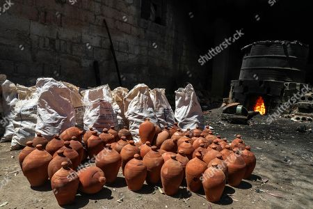 A stove full of Clay bowls for hookah water pipe which are roasted  inside the kiln firing at a traditional pottery workshop in Armanaz, Idlib Governorate, Syria, 09 July 2018. Armanaz town is famous for artisan crafts such as glass manufacturing and traditional pottery. Local clay is first placed under the sun to dry for at least fifteen days, after which it is ready to be made into a clay mixture. The mixture is shaped into different forms such as pots, jugs, jars and bowls for hookah water pipes. The shaped pottery is left to dry completely before being placed into a kiln to harden. Before the Syrian crisis, pottery from the town used to be exported to various countries, according to the workshop owner Aref Jammo, who has been working in the industry for more than 35 years. Aref inherited the craft from his father as the skill was passed down from generation to generation.