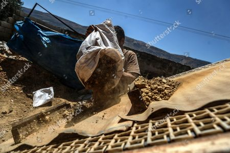 A worker carries a bag of jagged and rough stone to grind at a stone mill at a traditional pottery workshop in Armanaz, Idlib Governorate, Syria, 09 July 2018. Armanaz town is famous for artisan crafts such as glass manufacturing and traditional pottery. Local clay is first placed under the sun to dry for at least fifteen days, after which it is ready to be made into a clay mixture. The mixture is shaped into different forms such as pots, jugs, jars and bowls for hookah water pipes. The shaped pottery is left to dry completely before being placed into a kiln to harden. Before the Syrian crisis, pottery from the town used to be exported to various countries, according to the workshop owner Aref Jammo, who has been working in the industry for more than 35 years. Aref inherited the craft from his father as the skill was passed down from generation to generation.