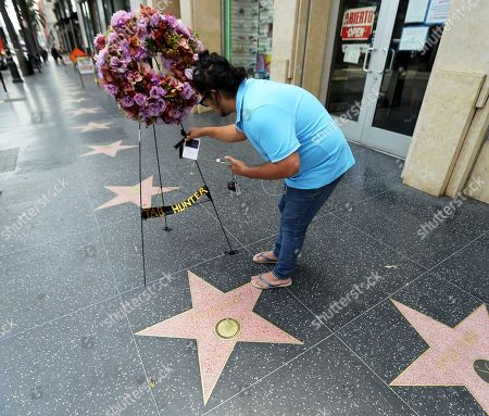 """Victor Lomillo dictates a blog as he looks at a wreath adorning the star honoring actor Tab Hunter on the Hollywood Walk of Fame in Los Angeles, . Hunter, the blond actor and singer who was a heartthrob for millions of teenagers in the 1950s with such films as """"Battle Cry"""" and """"Damn Yankees"""" and received new attention decades later when he revealed that he was gay, died Sunday, July 8. He was 86"""