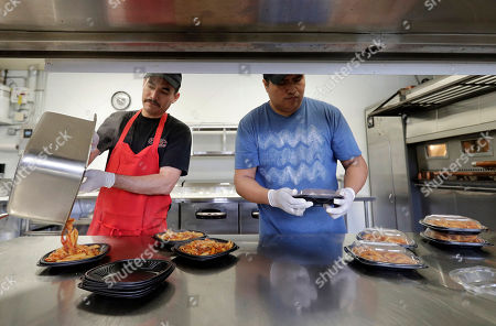 Miguel Gonzales, Oscar Garcia. This photo shows Miguel Gonzales, left, and Oscar Garcia prepare lunch at Piero's Pizza to go to Kipling Elementary School in Highland, Ill. Food-delivery services are remaking school lunch. Many parents still make their kids' lunch, of course, or sign up for a hot-lunch program through school. But others are ordering from companies that deliver meals to home or school