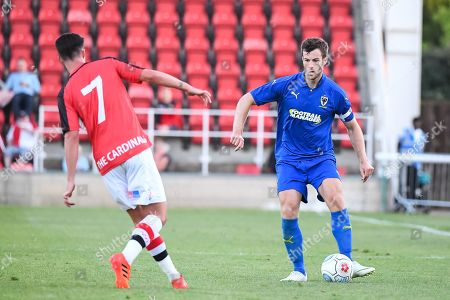 AFC Wimbledon Defender Jonathan Meades (3) and Woking Midfielder Bobson Bawling (7) in action during the Pre-Season Friendly match between Woking and AFC Wimbledon at the Kingfield Stadium, Woking. Picture by Stephen Wright