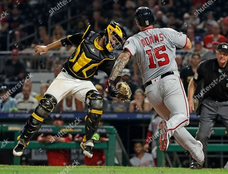 Pittsburgh Pirates catcher Elias Diaz, left, comes down a high relay throw in time to tag out Washington Nationals' Matt Adams (15) who was attempting to score on a double to right field by National's Daniel Murphy in the seventh inning of a baseball game in Pittsburgh
