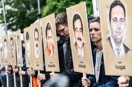 People hold banners with portraits of murdered migrants in front of the Higher Regional Court in Munich, Bavaria, Germany, 10 July 2018. A verdict in the trial of co-defendant Beate Zschaepe is to be announced on 11 July 2018, some five years after the trial started. Zschaepe is accused of being a founding member of the extreme right-wing National Socialist Underground (NSU) terror cell and faces charges of complicity in the murder of nine Turkish and Greek migrants and a policewoman between 2000 and 2007, as well as two bombings in migrant areas of Cologne, and 15 bank robberies.