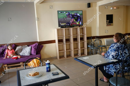 A woman watches France's Sylvain Chavanel riding breakaway on a TV during the fifth stage of the Tour de France cycling race over 204.5 kilometers (127 miles) with start in Lorient and finish in Quimper, France