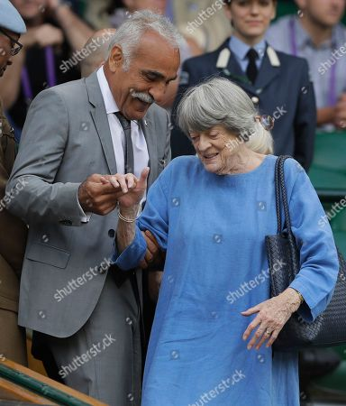 British actress Maggie Smith is helped to her seat by Iran tennis player Mansour Bahrami in the Royal Box on Centre Court at the Wimbledon Tennis Championships in London
