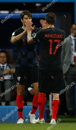 Croatia's Vedran Corluka, left, substitutes in for Croatia's Mario Mandzukic, right, during the semifinal match between Croatia and England at the 2018 soccer World Cup in the Luzhniki Stadium in Moscow, Russia
