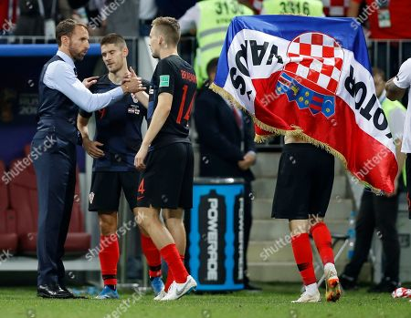 England head coach Gareth Southgate, left, shake hands with Croatia's Filip Bradaric, right after the semifinal match between Croatia and England at the 2018 soccer World Cup in the Luzhniki Stadium in Moscow, Russia