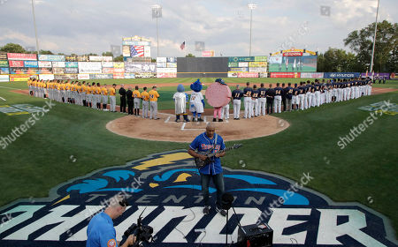 Former New York Yankees player Bernie Williams, center, plays the national anthem prior to the Eastern League All-Star Double-A baseball game, in Trenton, N.J