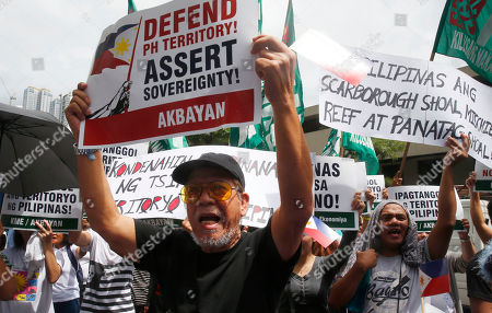 Stock Image of Protesters shout slogans during a rally at the Chinese Consulate to mark the second anniversary of the United Nations Permanent Court of Arbitration's decision upholding the Philippines' territorial rights in the disputed Spratlys Group of islands in the South China Sea, in Manila, Philippines. The ruling was shelved by President Rodrigo Duterte and was never recognized by China and continues instead to build military facilities on the disputed islands