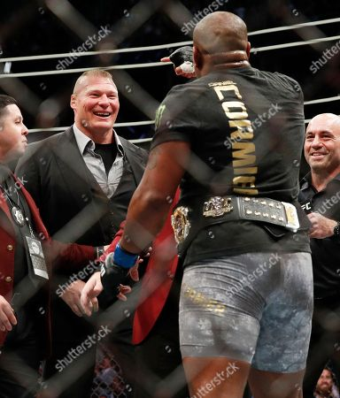 Brock Lesnar, left, taunts Daniel Cormier after Cormier's heavyweight title mixed martial arts bout at against Stipe Miocic at UFC 226, in Las Vegas