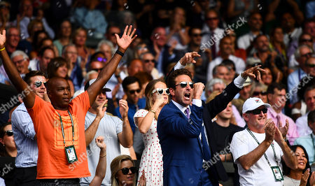 Former tennis player Justin Gimelstob, who is working with John Isner (centre), celebrates in John Isner's players box