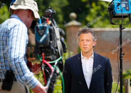 Tom Newton Dunn, Political Editor of the Sun Newspaper, right, waits to speak to Fox Television News network at Chequers, in Buckinghamshire, England, . In an interview with Sun newspaper, President Donald Trump slammed British Prime Minister Theresa May's plan for British departure from the Europe Union and praised her political rival Boris Johnson, who quit May's Cabinet this week over Brexit differences