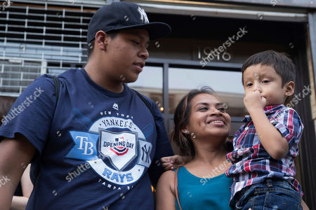 Rosayra Pablo Cruz, center, smiles at he sons 5-year-old Fernando, right, and 15-year-old Jordy outside the Cayuga Center, in New York
