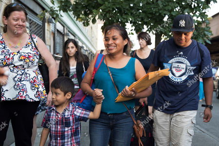 Julie Schwietert-Collazo, left, of Immigrant Families Together, walks with Rosayra Pablo Cruz, center, as she leaves the Cayuga Center with her sons 5-year-old Fernando, second from left, and 15-year-old Jordy, in New York
