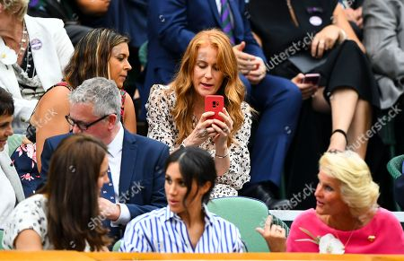 Stock Image of A member of the Royal Box, Iva Majoli (who is with Marion Bartoli) appears to take a photograph on her phone of Meghan Duchess of Sussex