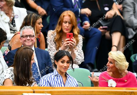 A member of the Royal Box, Iva Majoli (who is with Marion Bartoli) appears to take a photograph on her phone of Meghan Duchess of Sussex