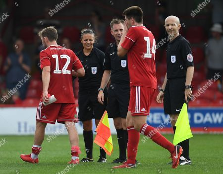 Assistant referee Lisa Rashid shakes hands with players at full time