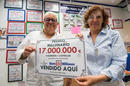 Maria Angeles Chacon (R), lottery outlet owner, and her husband Manuel Caballero hold a banner reading 'Millionaire Jackpot. 17,000,000. Five Numbers + 2 Stars. Sold Here' at their lottery outlet, where the Euromillion winning ticket was sold, in Seville, southern Spain, 14 July 2018. A person has won 17 million euro last 13 July.