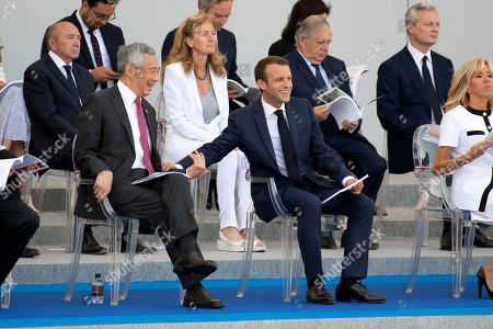 French President Emmanuel Macron (C) stands with Singapore's Prime Minister Lee Hsien Loong (L) his wife Brigitte Trogneux (C/R), French Labour Minister Muriel Penicaud, French Justice Minister Nicole Belloubet, French Junior Minister for the Digital Sector Mounir Mahjoubi, French Junior Minister for Foreign Affairs Jean-Baptiste Lemoyne, French Junior Minister for Economy Delphine Geny-Stephann, French Interior Minister Gerard Collomb, French Minister for the Territorial Cohesion Jacques Mezard and French Prime Minister Edouard Philippe during the annual Bastille Day military parade
