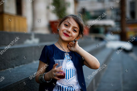 Syriana, 5, a Syrian girl poses for a picture as she drinks a traditional Arab cold drink called Jallab with her parents, in the Syrian capital Damascus, Syria