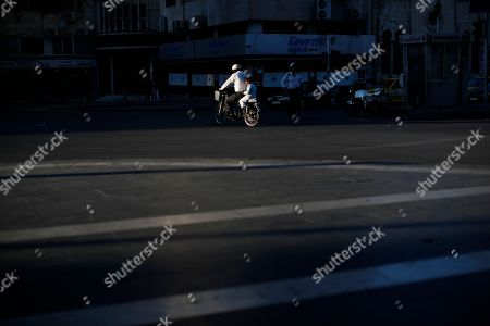 A Syrian man rides his scooter with his son as the sun sets in the Syrian capital Damascus, Syria