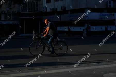 A Syrian man rides his bicycle as the sun sets in the Syrian capital Damascus, Syria