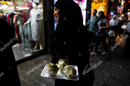 A Syrian woman buys ice cream at the Hamadiyah market, or souk in Arabic, that was named after the 34th Sultan of the Ottoman Empire Abdul Hamid II, in the Old City of Damascus, Syria
