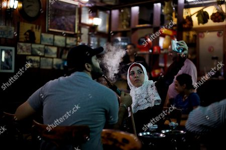 Stock Photo of A young Syrian woman takes a selfie at the al-Nafurah Café in the old city of Damascus, Syria