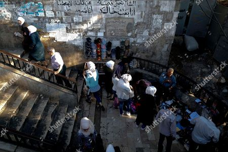 Syrian buy clothes from a street vendor under a bridge in the Syrian capital Damascus, Syria
