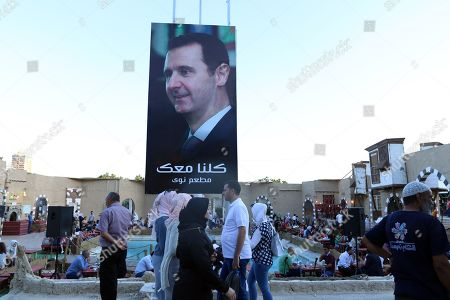 Syrians pass under a giant photo of Syrian President Bashar al-Assad as they visit the 'al-Sham Gathers us' marketing festival held in the Tishreen public park in Damascus, Syria, 14 July 2018. The event was held by the Damascus Governorate with the cooperation of the ministry of tourism