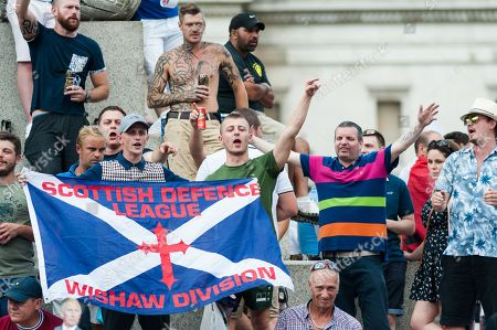 Supporters of far-right activist and former English Defence League leader Tommy Robinson stand on Nelson Column at Trafalgar Square after a rally in central London.