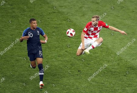 Croatia's Ivan Strinic, right, kicks the ball in front of France's Kylian Mbappe during the final match between France and Croatia at the 2018 soccer World Cup in the Luzhniki Stadium in Moscow, Russia