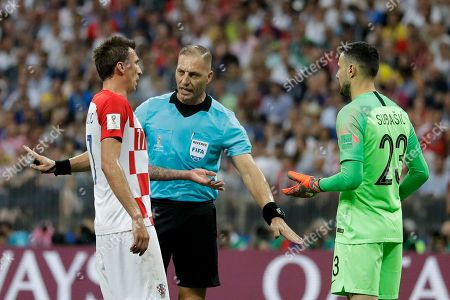 Referee Nestor Pitana from Argentina, center, talks to Croatia's Mario Mandzukic, left, and Croatia goalkeeper Danijel Subasic, right, after awarding a penalty for France during the final match between France and Croatia at the 2018 soccer World Cup in the Luzhniki Stadium in Moscow, Russia