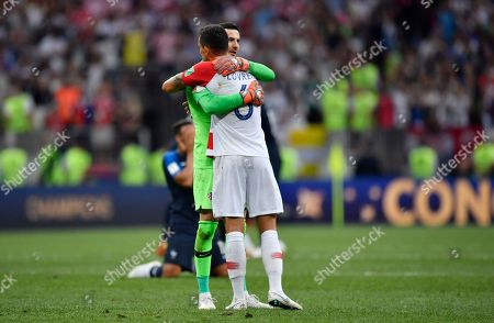Croatia goalkeeper Danijel Subasic comforts Croatia's Dejan Lovren, front, after losing during the final match between France and Croatia at the 2018 soccer World Cup in the Luzhniki Stadium in Moscow, Russia