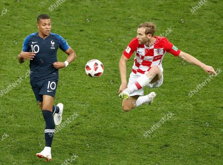 France's Kylian Mbappe, left, and Croatia's Ivan Strinic challenge for the ball during the final match between France and Croatia at the 2018 soccer World Cup in the Luzhniki Stadium in Moscow, Russia