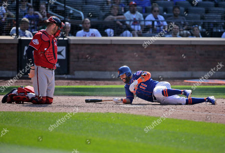 Jose Bautista, Jamie Burke. New York Mets' Jose Bautista, right, gets up after almost being hit by a pitch while Washington Nationals catcher Jamie Burke looks on during the ninth inning of the baseball game at Citi Field, in New York