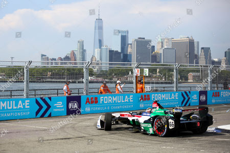Audi Sport Abt Schaeffler's Daniel Abt takes a hairpin turn during the second of two auto races in the Formula E championship, in the Brooklyn borough of New York. The skyline of Lower Manhattan is visible in the distance