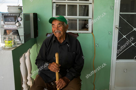 "Domingo Ortiz sits in his home, which has been without power since Hurricane Irma, in Adjuntas, Puerto Rico. Asked what is the first thing he will do after getting power back, he gestured toward an old boom box sitting on his porch. ""I'm going to turn that on and dance a little from happiness,"" he said"