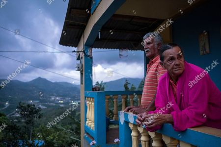 Stock Image of Power Adjuntas. Marta Bermudez Robles and her husband Juan Nunez stand on the balcony of their home which is still without power since Hurricane Irma and Maria in Adjuntas, Puerto Rico. With the expected, soon to come restoration of power to their home, Bermudez said she planned to celebrate no longer having to eat a diet of mostly rice, bananas and soup, or wash clothes by hand in a sink that they found on the street after Hurricane Irma