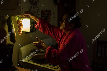 Marta Bermudez Robles, 66, hangs a lamp in her kitchen in Adjuntas, Puerto Rico, at her home that is still with electricity since Hurricane Irma and Maria. The only power Bermudez and her husband have had for 10 months is courtesy of a neighbor who threw over an extension cord connected to his generator that provides just enough power to light one bulb in the kitchen and another in the living room for a couple hours each day