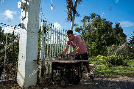Steven Vilella covers his generator outside his home that is still without electricity since Hurricane Irma and Maria in Adjuntas, Puerto Rico. Vilella is a 20-year-old delivery man with a wife and newborn at home