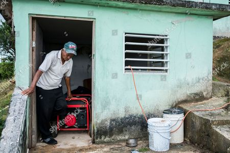 Jose Ortiz turns off his generator after using it for four hours at the home he shares with his father, Domingo, and brother, where they have not had power since Hurricane Irma in Adjuntas, Puerto Rico. The men have not had power since Hurricane Irma and have burned through more than 200 candles until a group of volunteers gave them solar lamps this past week