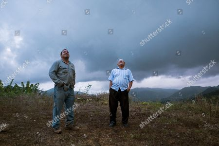 "Stock Photo of Retired resident Ramon Serrano, right, stands outside his home with a lineman from the Puerto Rico Power Authority as they watch a man restore power which was cut off by Hurricane Irma and Maria in Adjuntas, Puerto Rico. For the first time in 10 months, Serrano watched the 11 o'clock news on a recent weeknight and went to bed at midnight with his wife. ""It's the latest we've been up,"" said the 77-year-old"